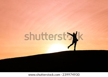 Woman standing on one leg with arms up in the air against a setting sun - stock photo