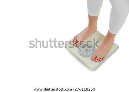 Woman standing on scales on white background - stock photo