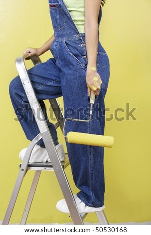 Woman standing on stepladder holding paint roller, side view, low section