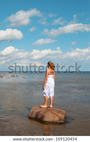 Woman standing on stone at sea coast.