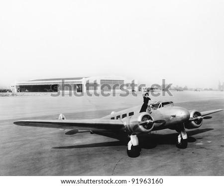 Woman standing on the propeller of an airplane waving - stock photo