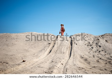 Woman standing on the sand hill with her shoes in her hand