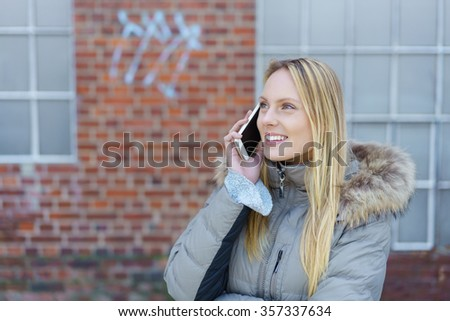 woman standing on the street in front of a brick wall using her mobile phone - stock photo