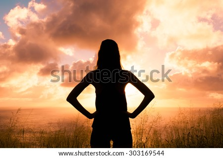 Woman standing on the top of the hill overlooking the ocean at sunrise - stock photo