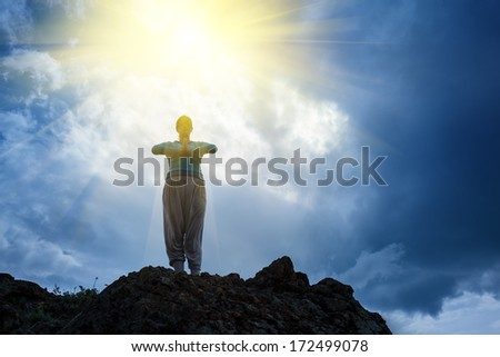Woman standing on top of mountain doing yoga meditation. Stormy sky background, sun rays shining on her. - stock photo