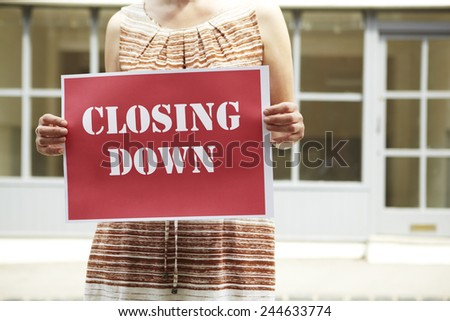 Woman Standing Outside Empty Shop Holding Closing Down Sign - stock photo