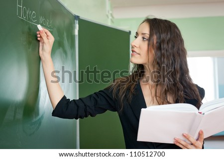 woman standing over green chalkboard at the classroom