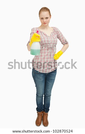 Woman standing while holding a spray bottle against white background - stock photo