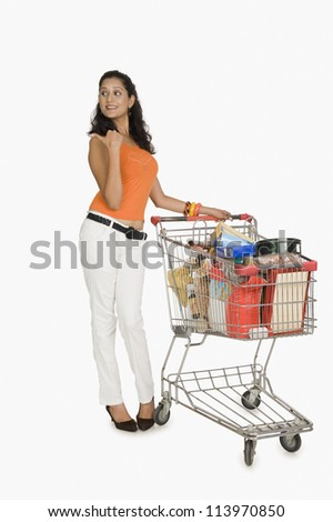 Woman standing with a shopping cart and pointing