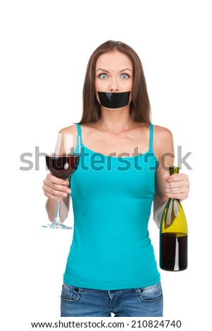 Woman standing with alcohol on white background. Beautiful young woman with sticky tape on her mouth - stock photo