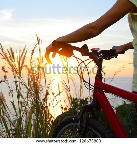 Woman standing with bicycle on a sea coast and enjoying sunset - stock photo