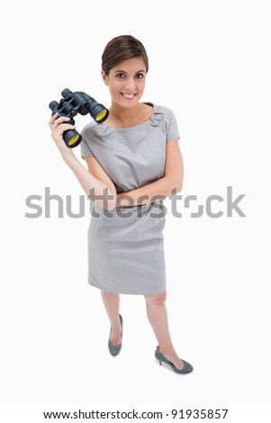 Woman standing with binoculars against a white background - stock photo