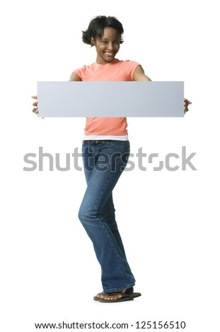 Woman standing with blank placard holding in front of her - stock photo