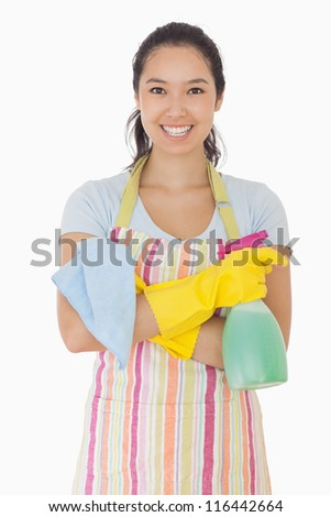 Woman standing with hands crossed holding cleaning products and smiling - stock photo