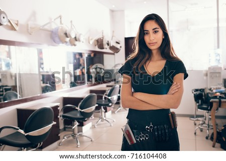 Woman standing with hands folded in her salon. Professional hairdresser with all the hairdressing accessories tied to her waist.