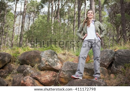 Woman standing with hands on hips in the forest - stock photo