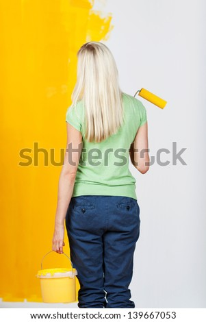 Woman standing with her back to the viewer and a tub of paint and roller in her hand contemplating a half painted wall with one half white and the other yellow in a before and after concept