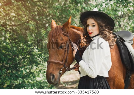 Woman standing with horse near forest and touching to horse face