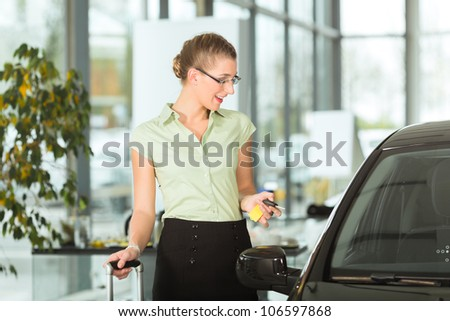 Woman standing with key next to her new bought or rental car - stock photo