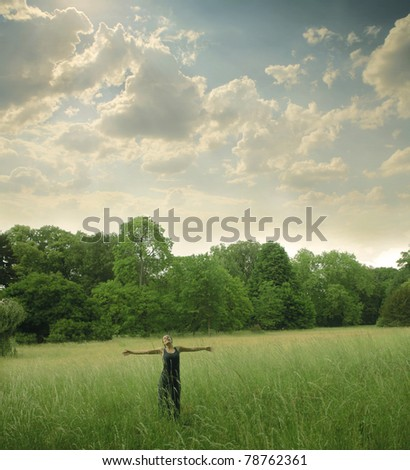 Woman standing with open arms on a green meadow - stock photo