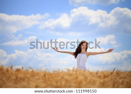 Woman  standing with outstretched arms in wheat field , freedom concept