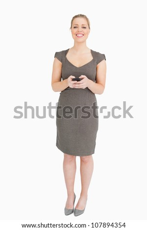 Woman standing with phone in her hands against white background - stock photo