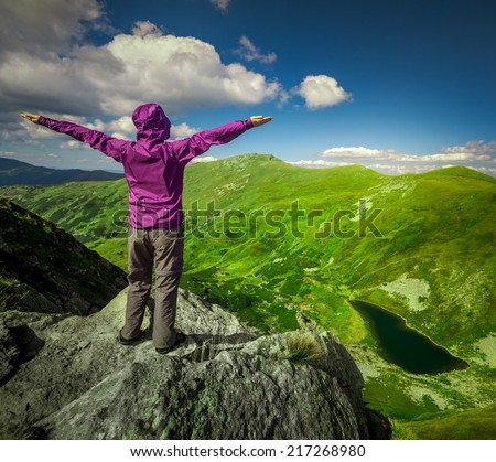 Woman standing with raised hands on top of a mountain. Carpathians, Ukraine - stock photo