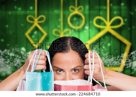 Woman standing with shopping bags against blurred christmas background - stock photo