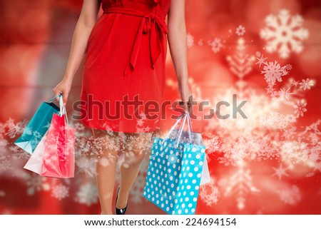 Woman standing with shopping bags against blurred snowflakes on planks - stock photo