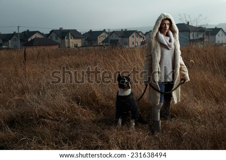 woman standing with staffordshire terrier in fields behind country town - stock photo
