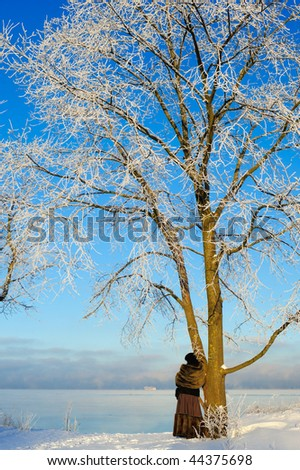 Woman stands near a tree on the bank of a frozen sea