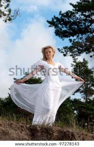 Woman stands near precipice. Wind blows the white dress.