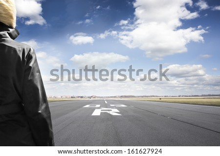 Woman stands on airport runway looking to the horizon - stock photo