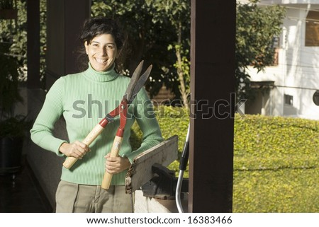 Woman stands on patio showing hedge trimmer. She is smiling at camera. Horizontally framed photo. - stock photo