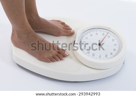 Woman stands on weighing scales isolated on white