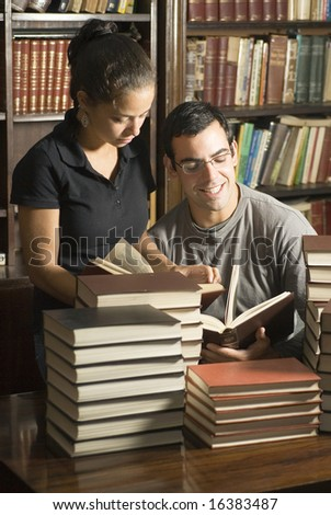Woman stands while man sits in library. They are reading books with stacks of books on table. Vertically framed photo. - stock photo