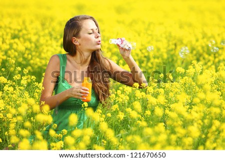 woman start soap bubbles on yellow flower field - stock photo