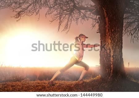 woman starting her run at sunrise warming up - stock photo