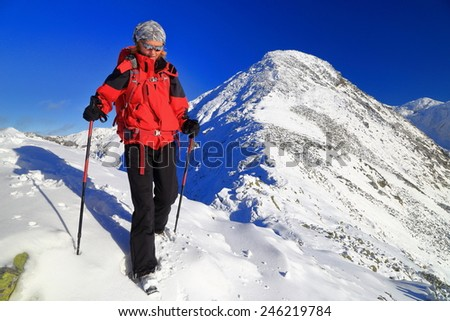 Woman stepping on snow covered mountain in sunny winter day - stock photo