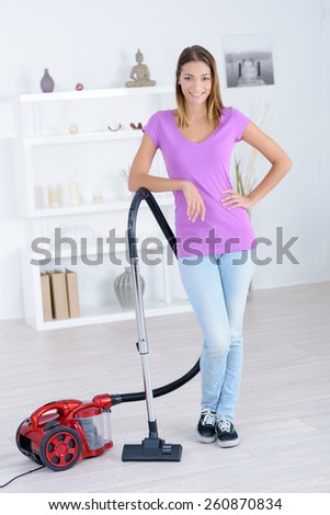 Woman stood with a vacuum cleaner - stock photo