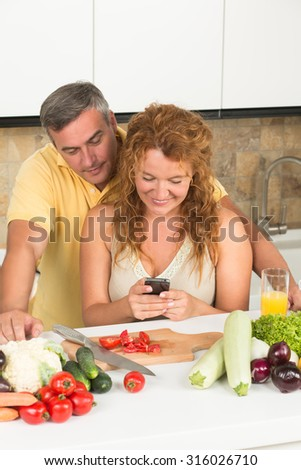 Woman stopped cooking to read the message in her mobile phone. Man in wauiting for her behind and looking into the phone.