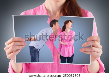 Woman stopping man from kissing against grey vignette - stock photo