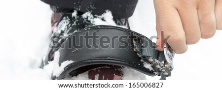 Woman Strapping into Snowboard