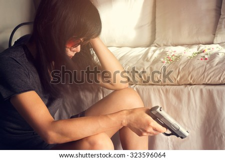 woman stress and depressed of her sickness, she decided to kill herself with a gun in hand  - stock photo