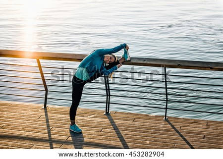 Woman stretching after training outdoors during sunset - stock photo