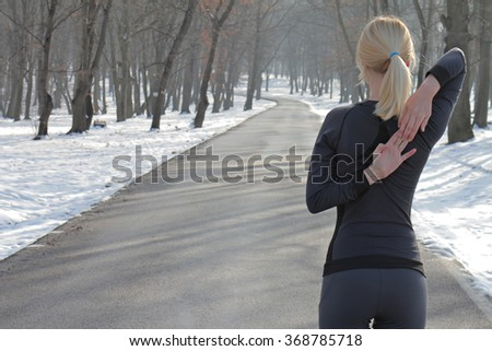Woman stretching before  workout outdoors on cold  winter day. Jogging, sport, fitness, active lifestyle concept, cold weather training - stock photo