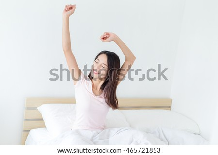 Woman stretching hand in bed