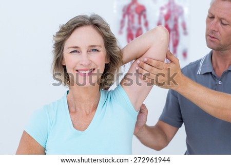 Woman stretching her arms with her doctor in medical office - stock photo