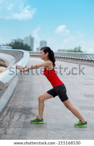 Woman stretching her calf muscles outdoors, side view - stock photo