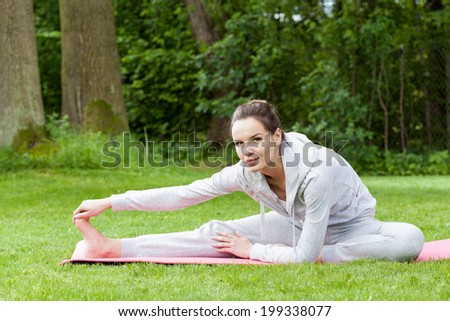 Woman stretching her legs on the open air
